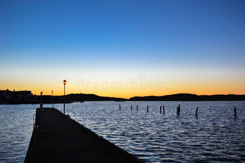 在金黄日落的路灯柱和山剪影 免版税库存照片