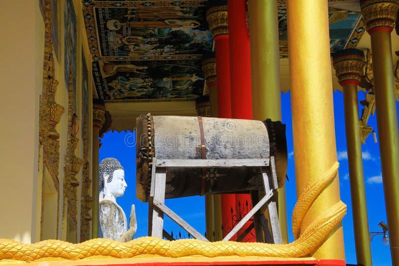 在金黄柱子、鼓和白色菩萨雕象的看法反对在佛教寺庙-在马德望附近的Wat Ek Phnom的天空蔚蓝,柬埔寨 免版税库存图片