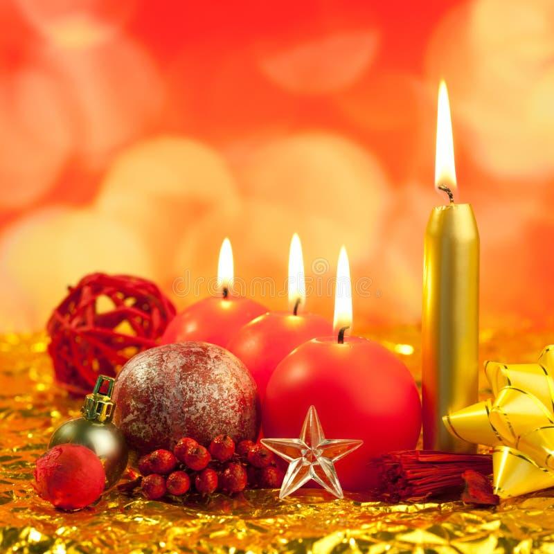 在金黄bokeh光的圣诞节红色蜡烛 免版税图库摄影
