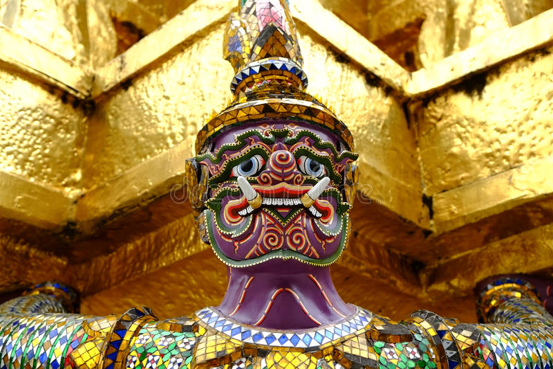 在金黄塔下的紫色巨人雕象 图库摄影
