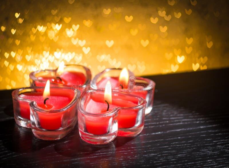 在金黄心脏bokeh的红色燃烧的心形的蜡烛