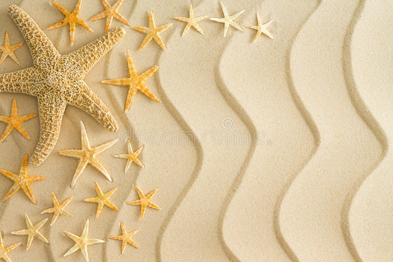 在金黄海滩沙子的海星与波浪线 免版税库存照片