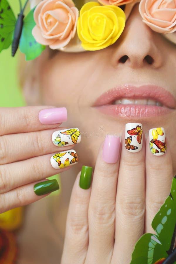 在钉子的多彩多姿的修指甲与蝴蝶设计  皇族释放例证