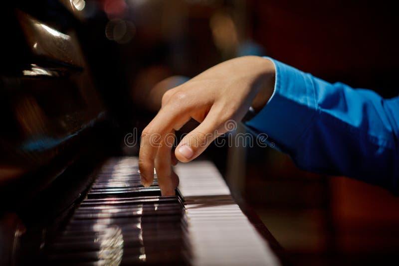 在钢琴的一只男性手 棕榈在钥匙说谎并且弹奏键盘仪器在音乐学校中 学生学会 免版税图库摄影