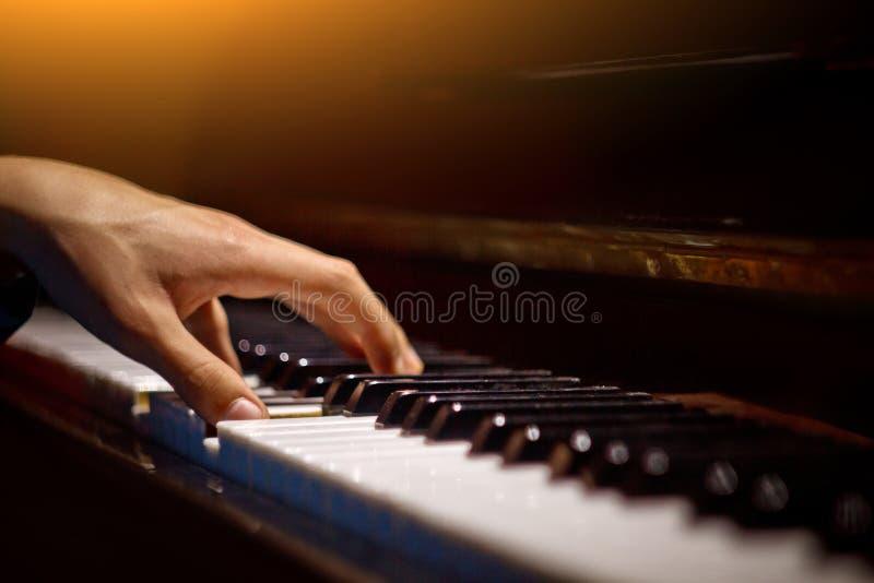 在钢琴的一只男性手 棕榈在钥匙说谎并且弹奏键盘仪器在音乐学校中 学生学会 免版税库存图片