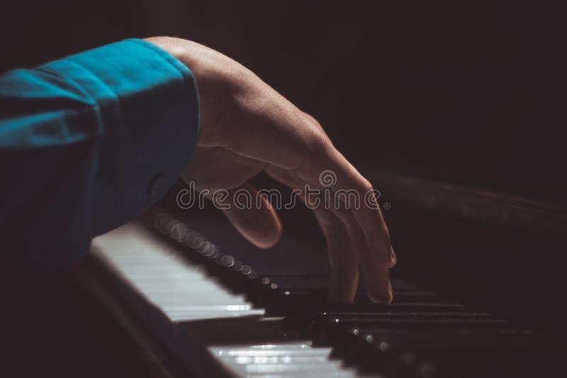 在钢琴的一只男性手 棕榈在钥匙说谎并且弹奏键盘仪器在音乐学校中 学生学会 库存图片
