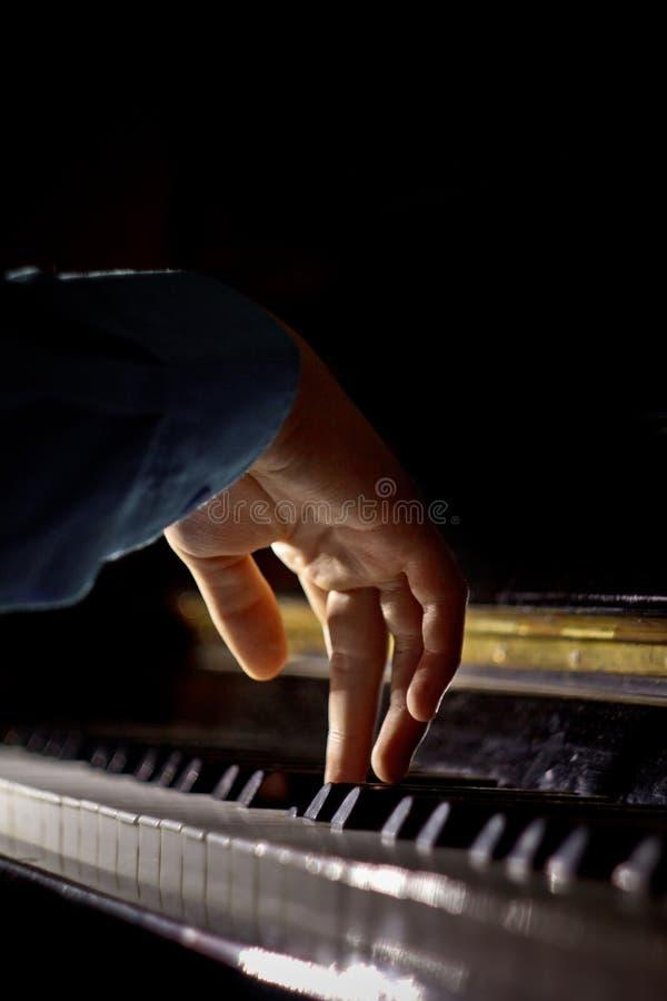 在钢琴的一只男性手 棕榈在钥匙说谎并且弹奏键盘仪器在音乐学校中 学生学会 库存照片