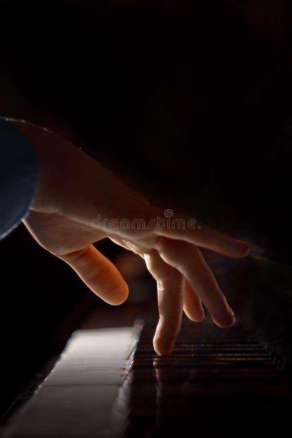 在钢琴的一只男性手 棕榈在钥匙说谎并且弹奏键盘仪器在音乐学校中 学生学会 免版税库存照片