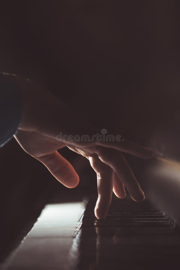 在钢琴的一只男性手 棕榈在钥匙说谎并且弹奏键盘仪器在音乐学校中 学生学会 图库摄影