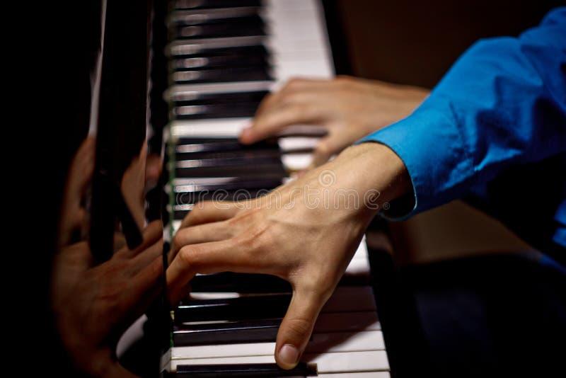 在钢琴的两只男性手 棕榈在钥匙横向说谎并且弹奏键盘仪器在音乐学校中 学生学会 免版税图库摄影
