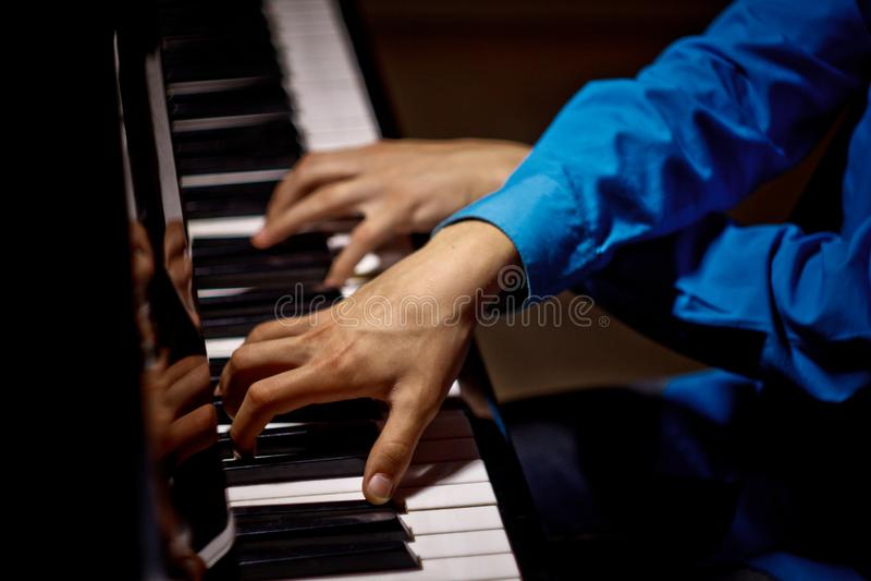 在钢琴的两只男性手 棕榈在钥匙横向说谎并且弹奏键盘仪器在音乐学校中 学生学会 库存照片