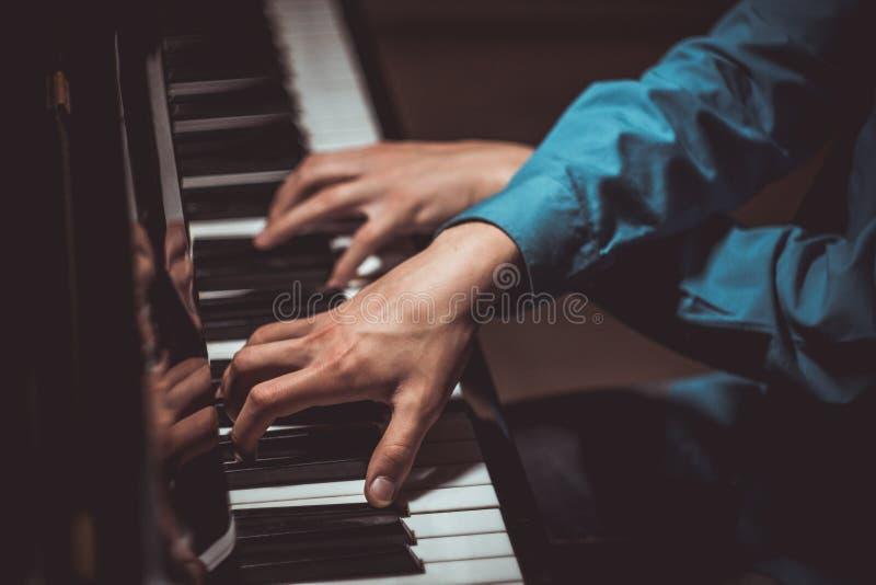 在钢琴的两只男性手 棕榈在钥匙横向说谎并且弹奏键盘仪器在音乐学校中 学生学会 库存图片