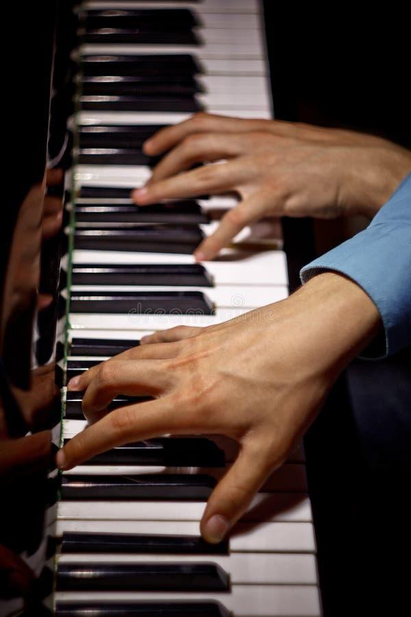 在钢琴的两只男性手 棕榈在钥匙横向说谎并且弹奏键盘仪器在音乐学校中 学生学会 免版税库存照片