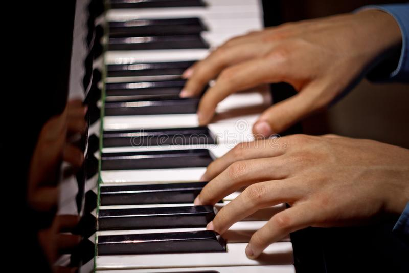 在钢琴的两只男性手 棕榈在钥匙说谎并且弹奏键盘仪器在音乐学校中 学生学会使用 免版税库存图片