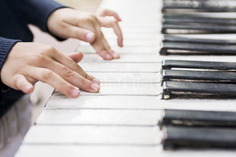 在钢琴的钥匙的儿童的手 孩子的钢琴培训班 库存图片