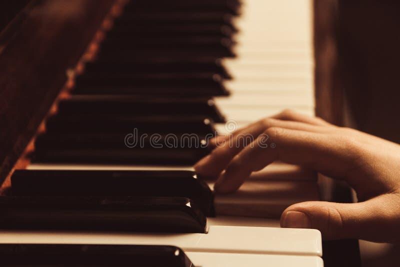 在钢琴钥匙的手 在减速火箭的样式的照片钢琴 免版税库存照片