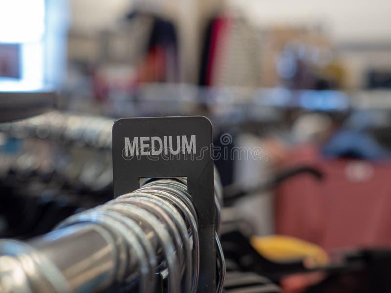 在钢衣物机架的中等部分标志有挂衣架的在百货店 图库摄影