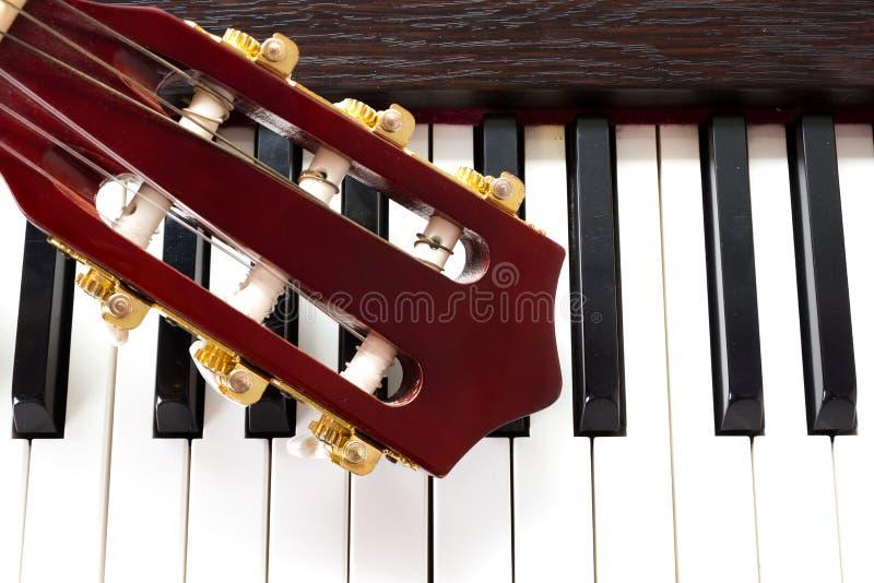 在钢琴关键字的吉他脖子 免版税库存图片