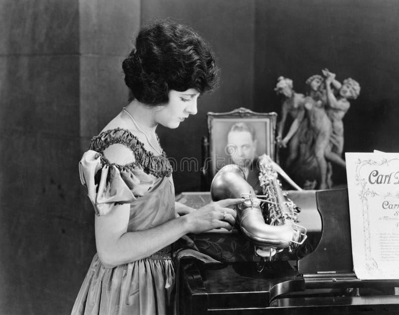 在钢琴的妇女感人的萨克斯管(所有人被描述不更长生存,并且庄园不存在 供应商保单ther 免版税图库摄影