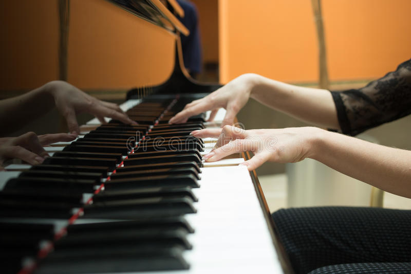 在钢琴键盘的妇女的手  女孩戏剧 库存照片