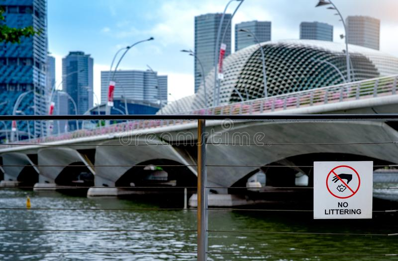 在铁丝网的没有乱丢的标志在河旁边在有摩天大楼企业大厦的街市 不投掷的垃圾的标志 图库摄影
