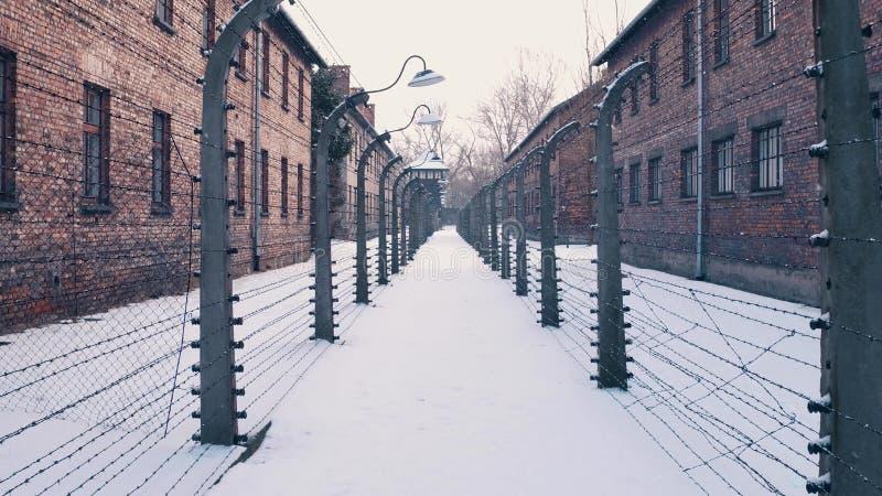 在铁丝网篱芭之间 奥斯威辛比克瑙、德国纳粹集中和灭绝野营 落的营房 免版税库存照片