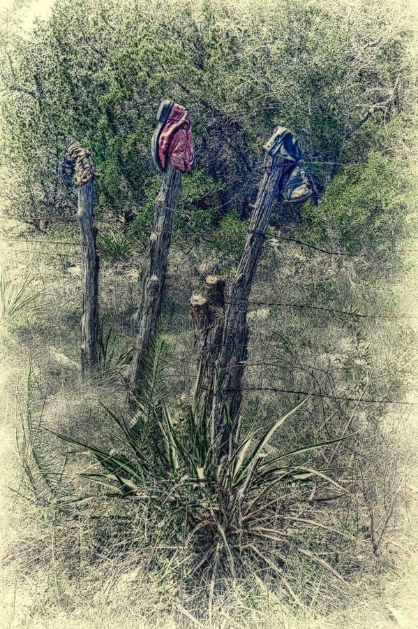 在铁丝网篱芭岗位的牛仔靴 库存图片