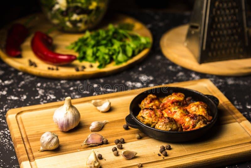 在铁平底锅的丸子在一个木板用大蒜和干胡椒 图库摄影