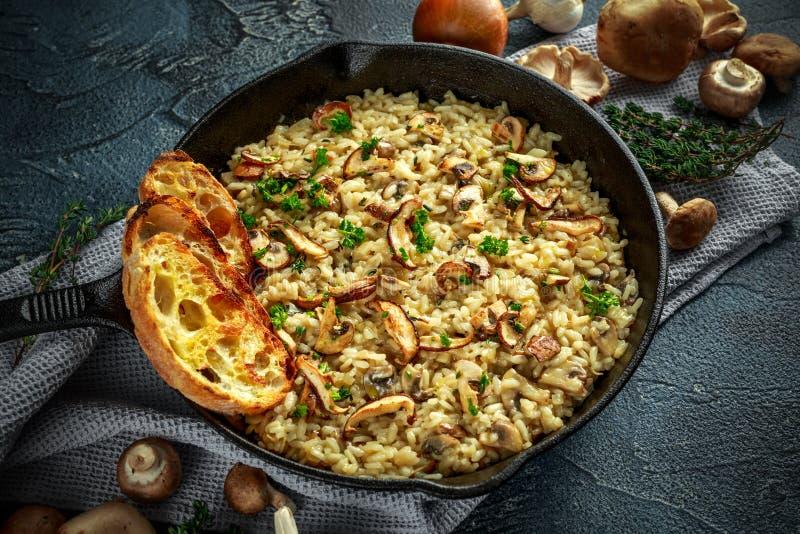 在铁平底锅的蘑菇意大利煨饭用草本和帕尔马干酪 免版税库存图片