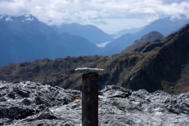 在铁管安置的石头在圆锥形小山顶部在哈里斯马鞍在Routeburn巨大步行在Fiordland,新 免版税库存照片
