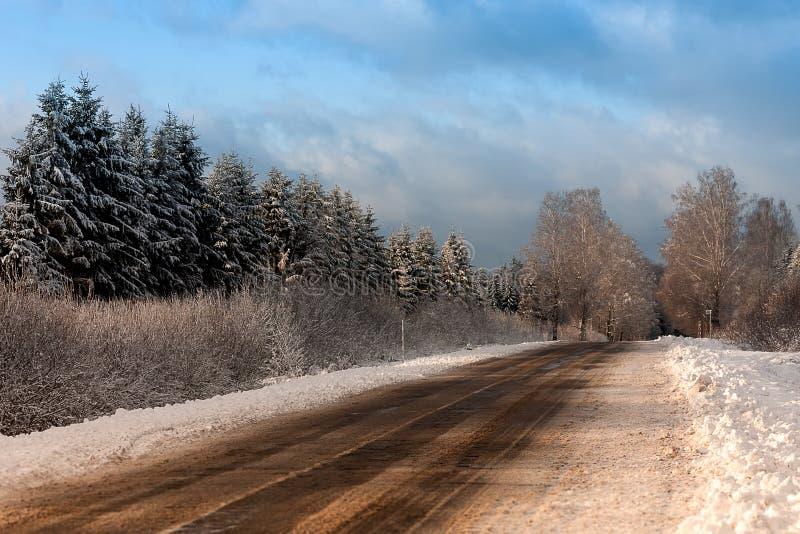 在铁路路附近的城市发光雪星期日对冬天木头 免版税图库摄影