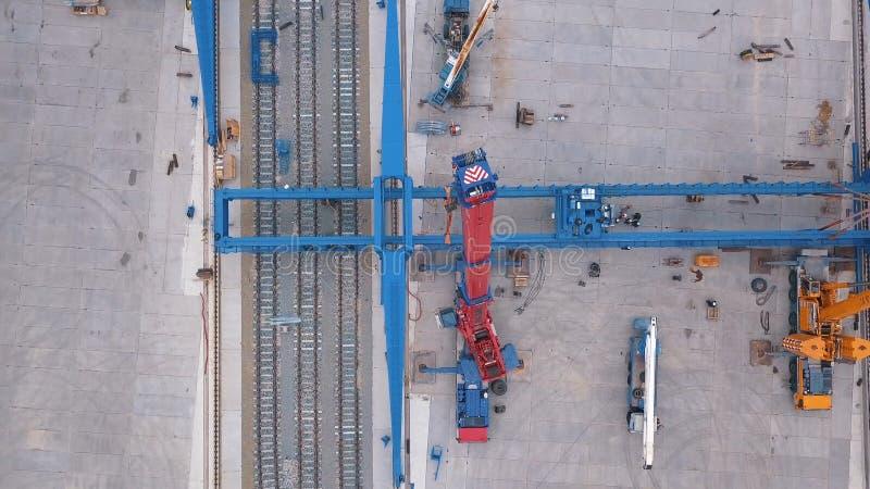 在铁路附近被安装的红色和黄色举的起重机鸟瞰图在工业区 ?? 建筑和 免版税库存照片