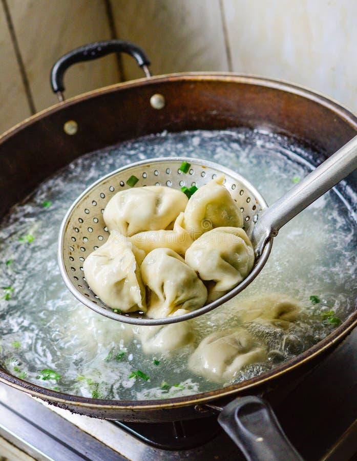 在铁锅的中国人厨师煮沸的饺子 免版税库存照片