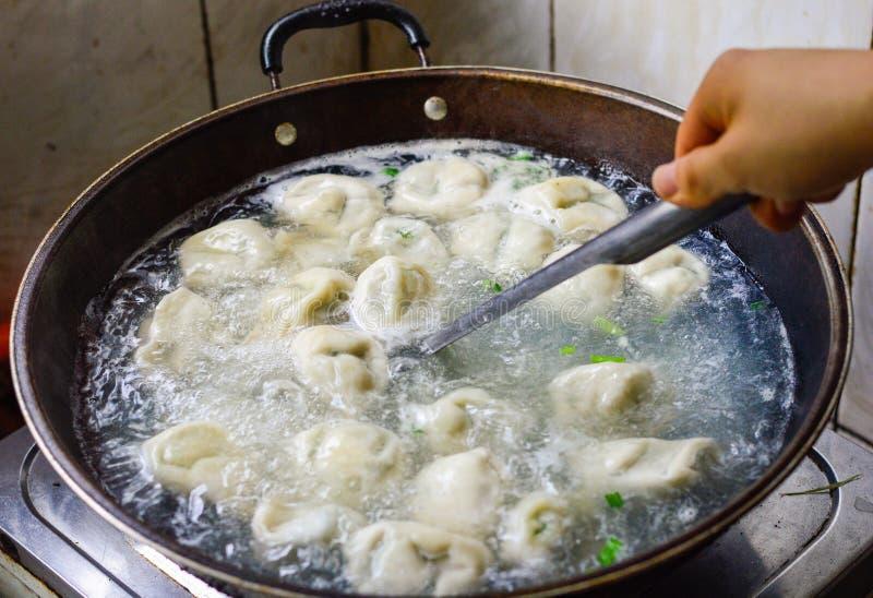 在铁锅的中国家庭厨师Boilded饺子 免版税库存照片