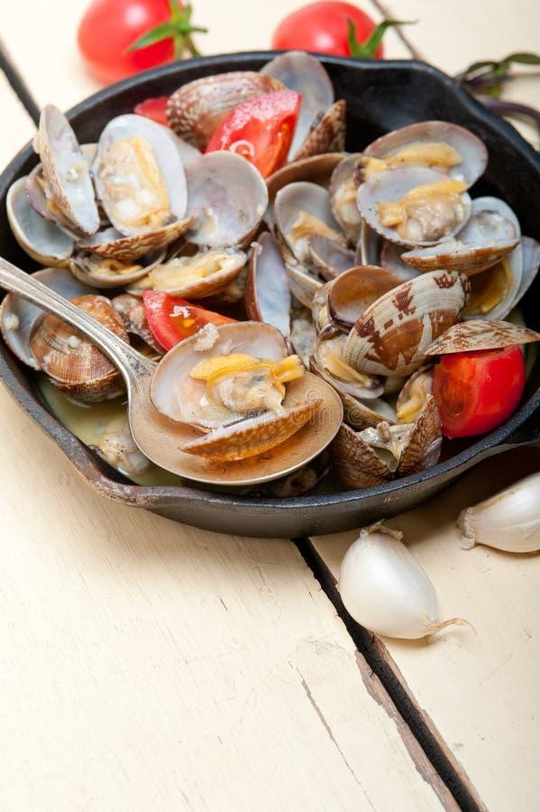 在铁长柄浅锅的新鲜的蛤蜊 库存照片