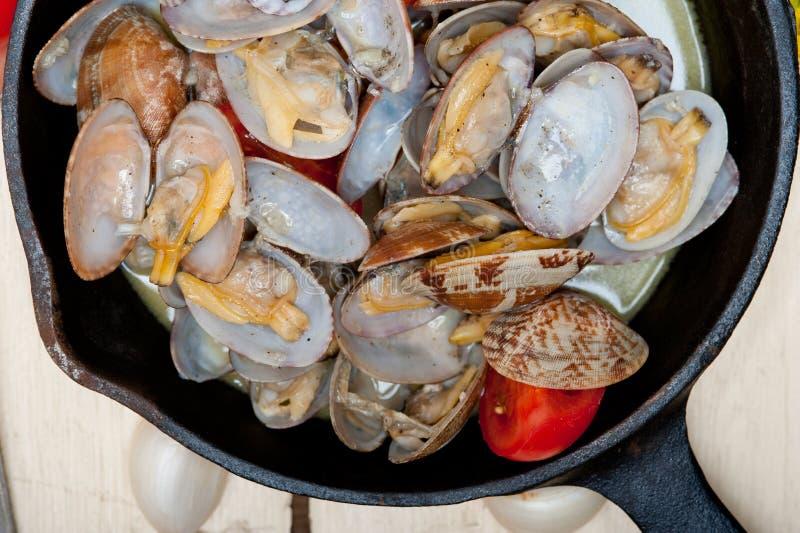 在铁长柄浅锅的新鲜的蛤蜊 免版税库存照片