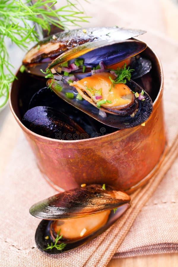 在铜平底深锅的淡菜 库存照片