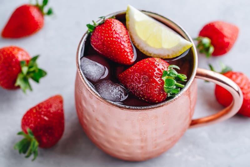 在铜杯子的刷新的被冰的莫斯科骡子酒精鸡尾酒用草莓和柠檬 免版税库存照片