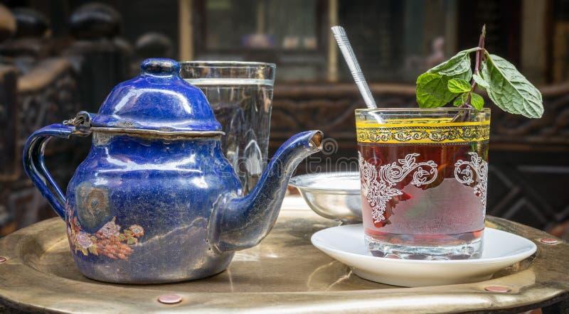 在铜桌,开罗,埃及上的传统薄荷的茶具 库存照片