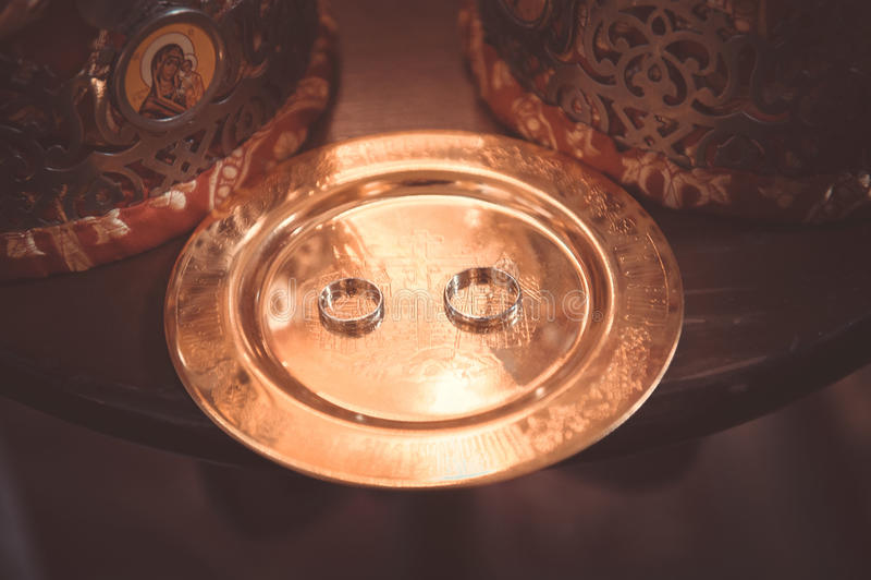 在铜盘子的两个简单的金婚圆环 免版税库存照片