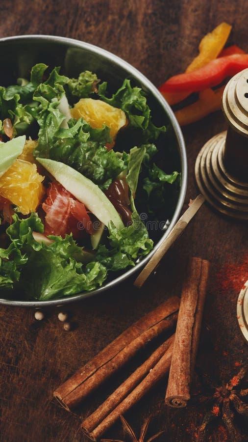 在铜碗的新鲜的水果和蔬菜沙拉用cinamon棍子 免版税库存照片