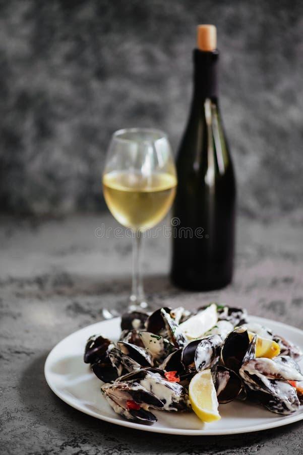 在铜罐和白葡萄酒的淡菜在石桌上 免版税库存照片