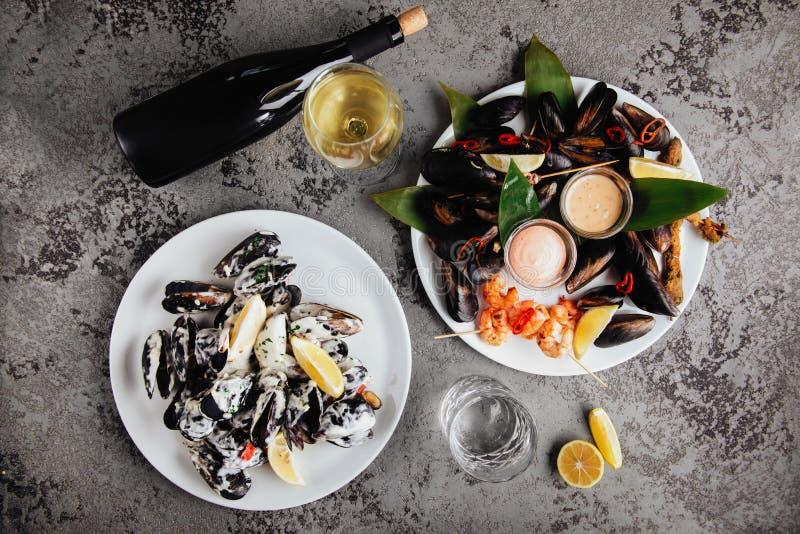 在铜罐和白葡萄酒的淡菜在石桌上 免版税库存图片