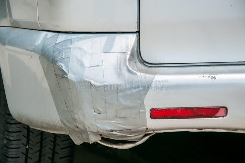 在银色搬运车上的残破的塑料尾端防撞器胶合与胶带 免版税库存图片