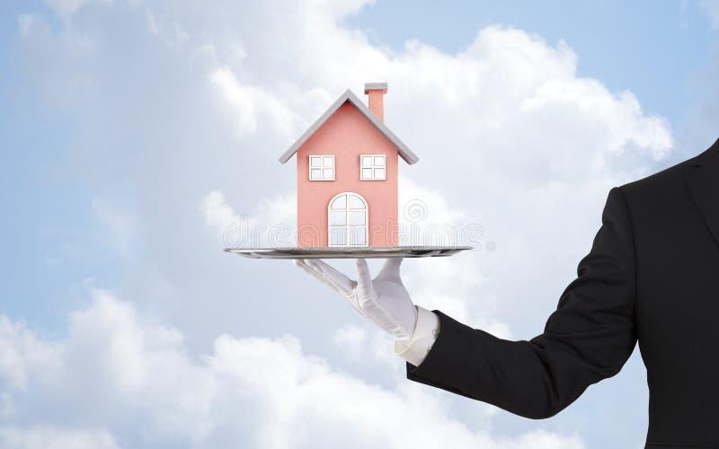 在银色盘子的商人提供的房子模型 库存图片