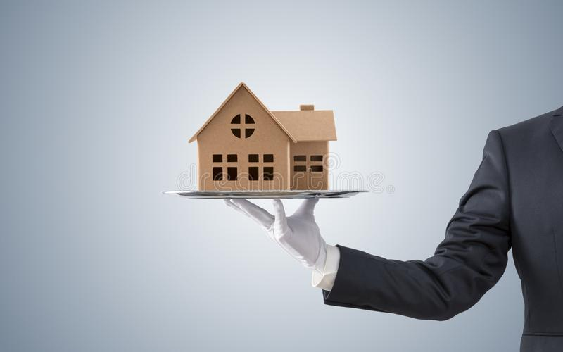 在银色盘子的商人提供的房子模型 库存照片