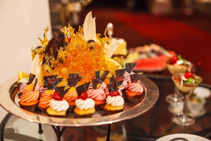 在银色盘子的奶油色杯形蛋糕分类涂黄油有糖果艺术装饰的 旅馆餐馆食物承办酒席服务自助餐鸡尾酒banqu 库存图片