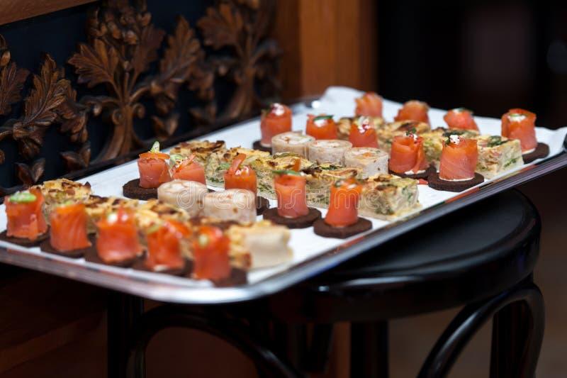 在银色盛肉盘的开胃菜在木椅子 免版税图库摄影