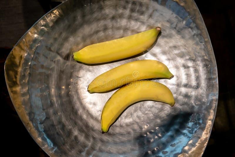 在银色碗的三个香蕉反对黑背景 免版税库存照片