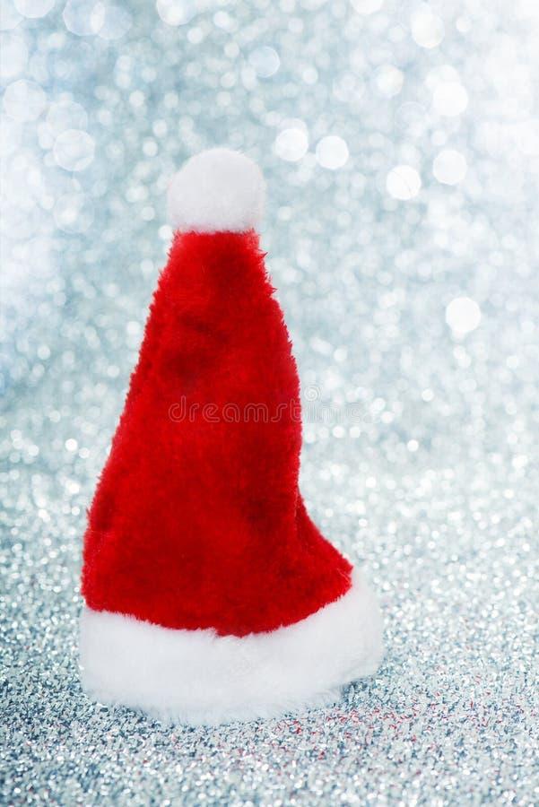 在银色背景的一点圣诞节帽子 免版税库存照片